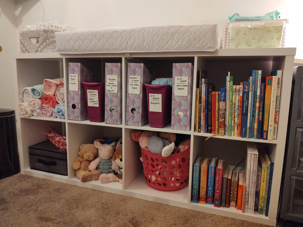 cubbies with changing pad, baby clothes, stuffed toys, and books